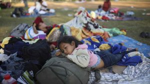 """Nayeli Zelaya from El Salvador, rests alongside her two sleeping siblings, at the sports club where Central American migrants traveling with the annual """"Stations of the Cross"""" caravan are camped out, in Matias Romero, Oaxaca State, Mexico, Wednesday, April 4, 2018. The children's father Elmer Zelaya said the family is awaiting temporary transit visas that would allow them to continue to the U.S. border, where they hope to request asylum and join relatives in New York. (AP Photo/Felix Marquez)"""